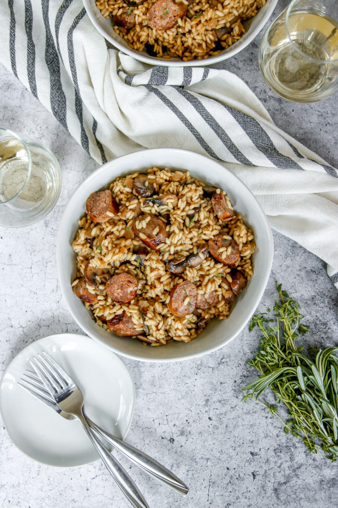 an overhead shot of two bowls of sausage mushroom risotto and two wine glasses