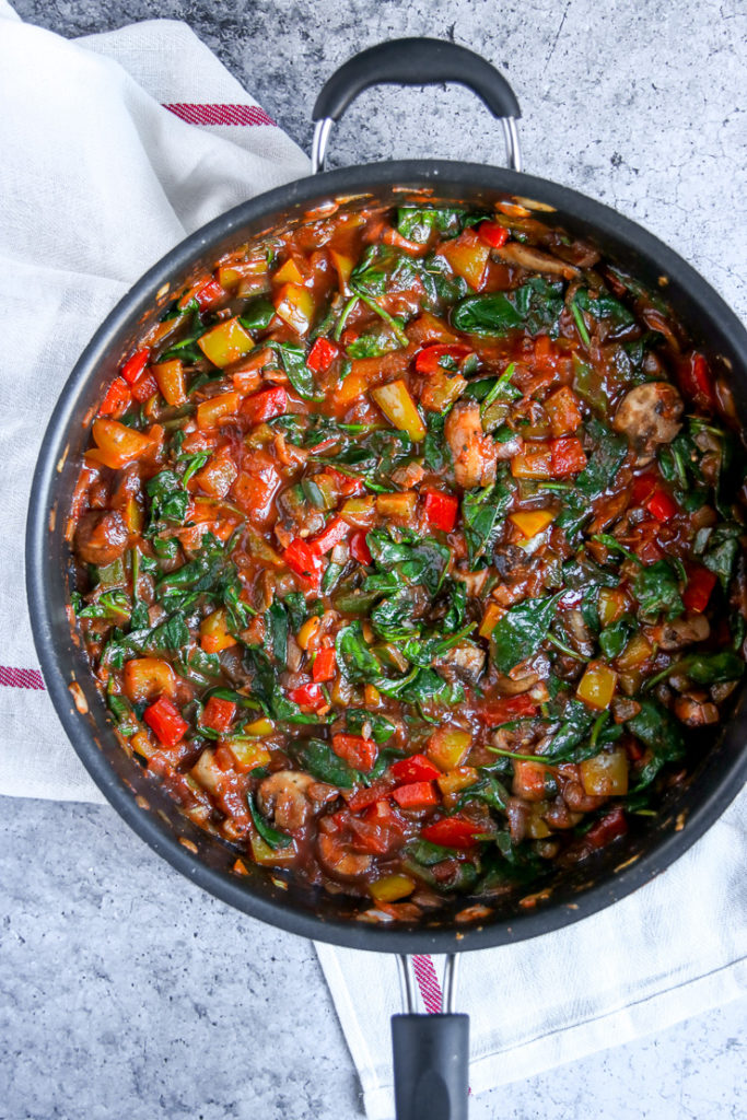 a skillet of sauteed spinach, mushrooms, and peppers