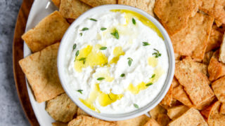 a bowl of whipped feta dip sitting on a plate with pita chips