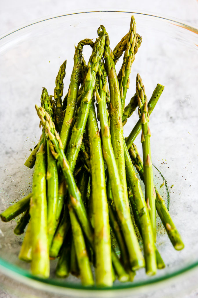a glass bowl of asparagus stalks with olive oil, salt and pepper on them