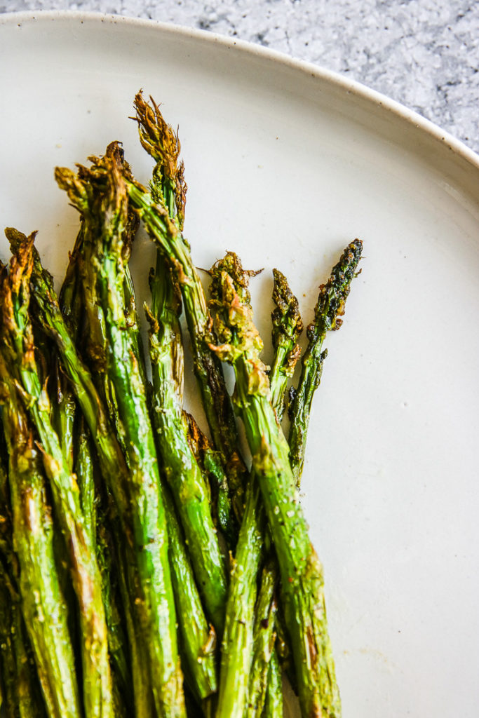 a close up of the roasted tips of the air fried asparagus stalks
