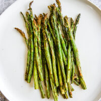a white plate full of asparagus right from the air fryer
