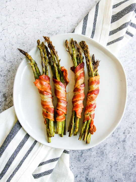 a plate of air fryer bacon wrapped asparagus on a grey and white napkin