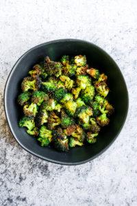 a black bowl of air fryer broccoli on a grey background