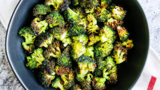 a bowl of air fryer broccoli in a black bowl on a red and white napkin