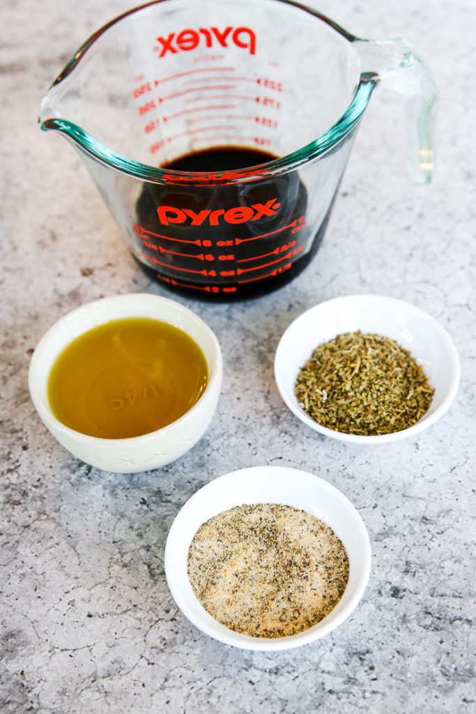 a pyrex measuring cup of balsamic vinegar, and bowls of olive oil, Italian seasonings, and salt and pepper