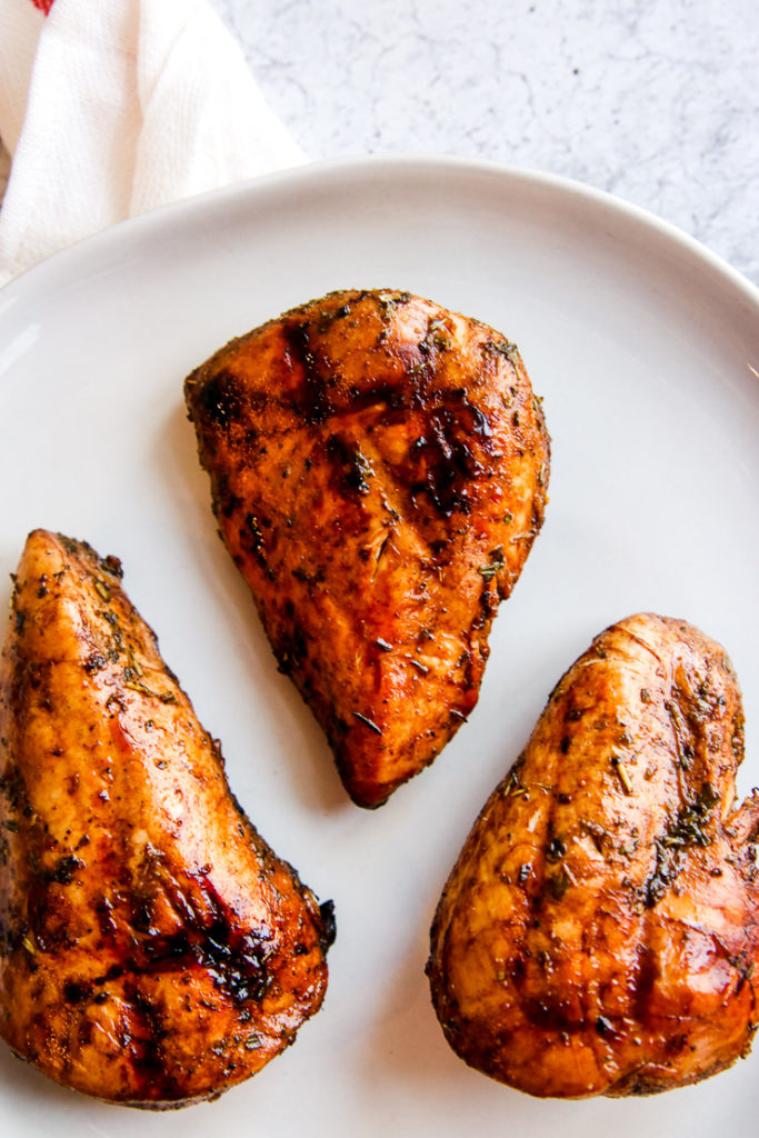 three balsamic grilled chicken breasts on a white plate