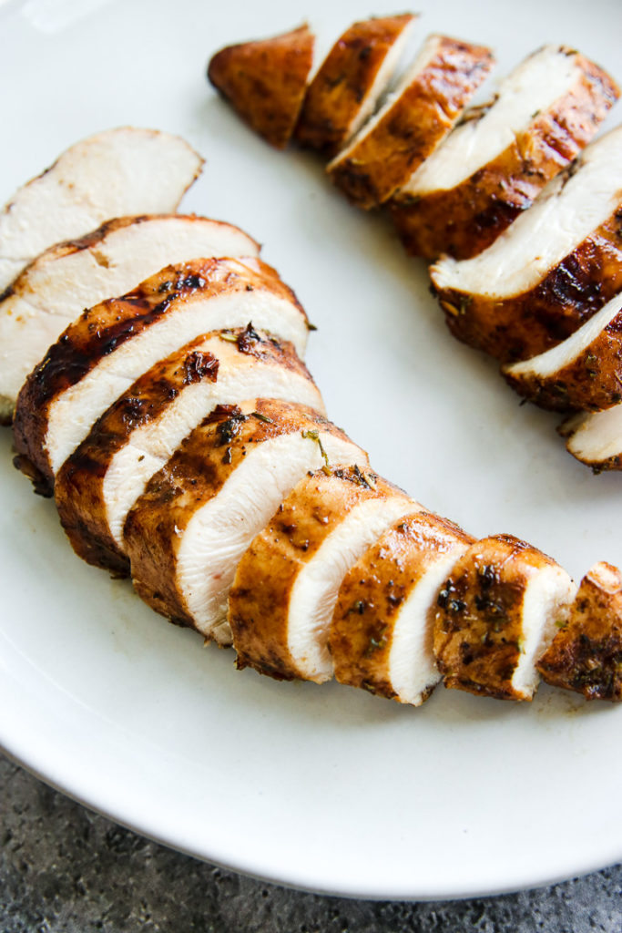 a close up of two sliced balsamic grilled chicken breasts on a white plate