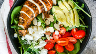 two black bowls of balsamic grilled chicken salad with feta, sliced almonds, tomatoes, and avocado