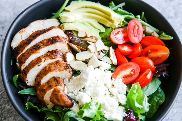 a close image of the sliced chicken breast, crumbled feta, slivered almonds, sliced cherry tomatoes, and sliced avocado on a spring mix salad