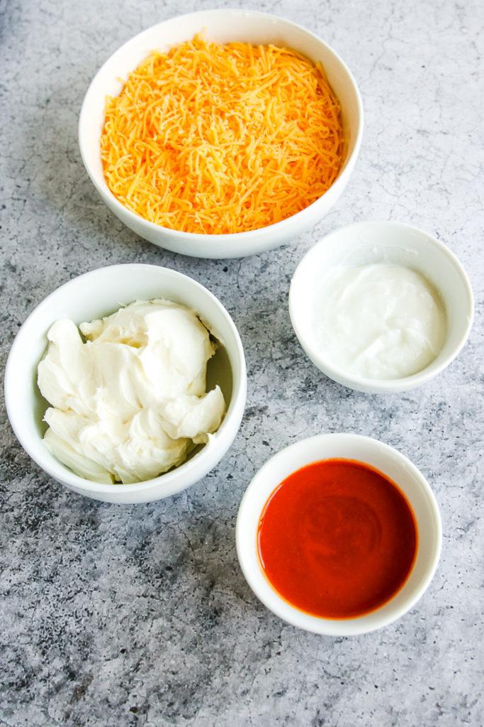 four bowls of shredded cheddar cheese, neufchatel cheese, greek yogurt, and buffalo sauce