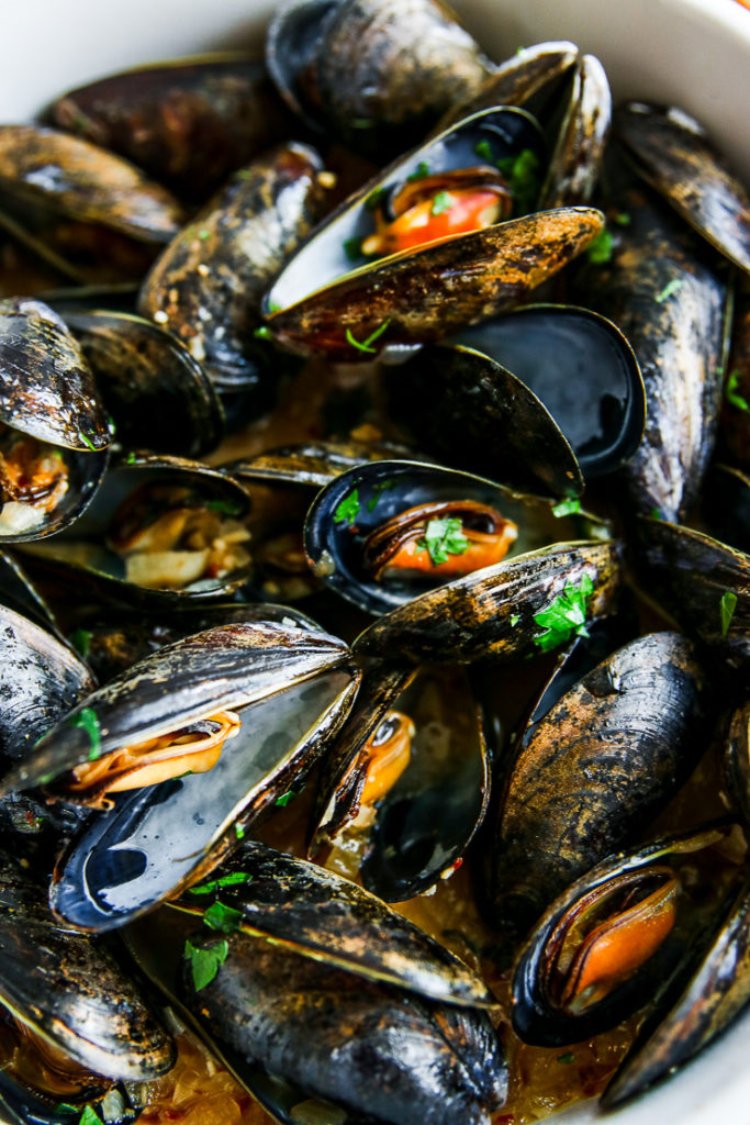 a close up of cooked garlic butter mussels sprinkled with parsley