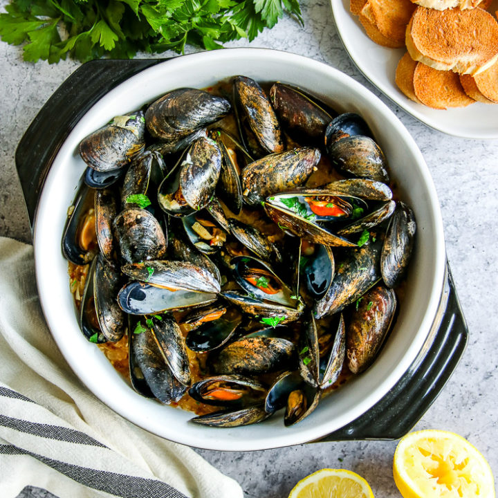 a saute pan full of garlic butter mussels next to parsley, toasted bread slices, and lemon halves