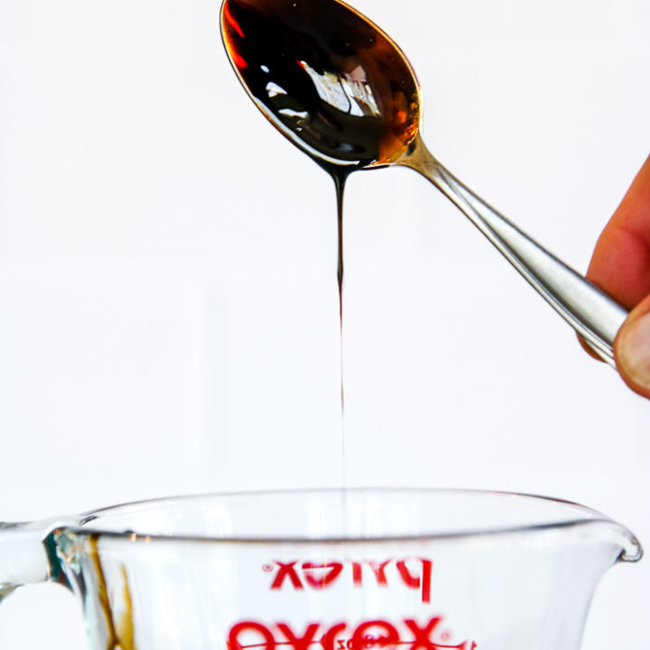 a spoon dipped in balsamic reduction over the pyrex