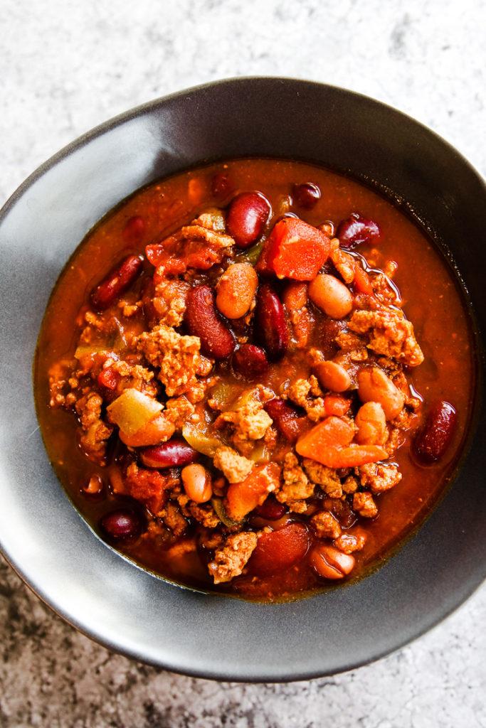 a grey bowl of instant pot ground turkey chili on a grey background