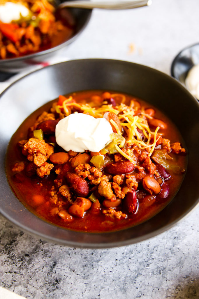 a close up of a grey bowl of instant pot ground turkey chili with a dollop of sour cream on top