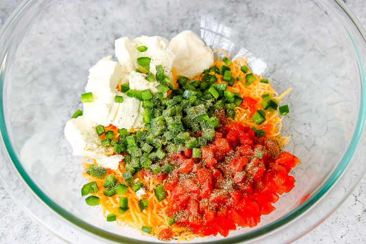 a glass bowl of shredded cheese, diced pimentos, diced jalapenos, and cream cheese with seasonings on top