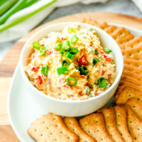 a bowl of jalapeno pimento cheese with sliced green onions on top next to crackers and full green onions