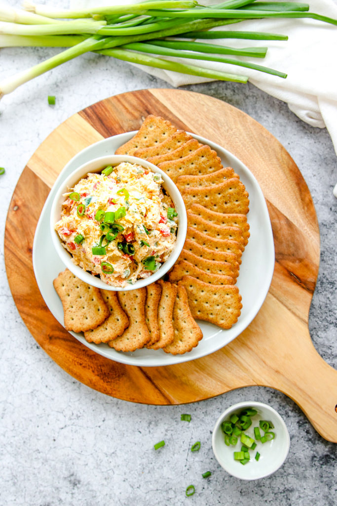 an overhead shot of a circle cutting board with a plate of crackers and bowl of jalapeno pimento cheese