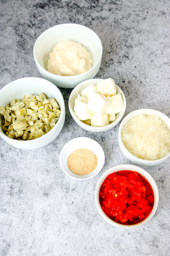 white bowls full of prepared artichokes, mayo, cream cheese, seasonings, parmesan, and roasted red peppers