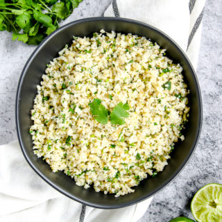 a black bowl on a striped napkin with cilantro lime cauliflower rice in it