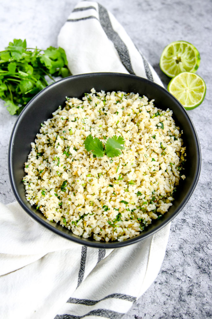 a black bowl of cilantro lime cauliflower rice next to a bunch of cilantro and limes