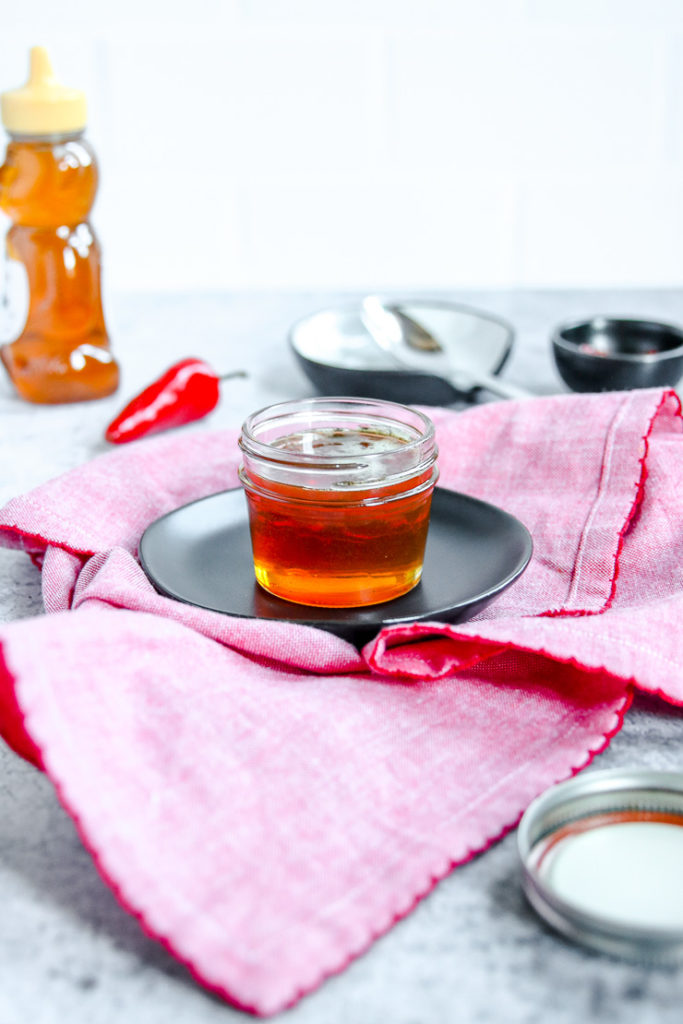 a glass jar of hot honey on a black plate on a red napkin