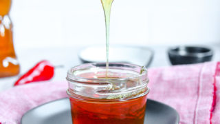 a spoon drizzling hot honey into a glass jar