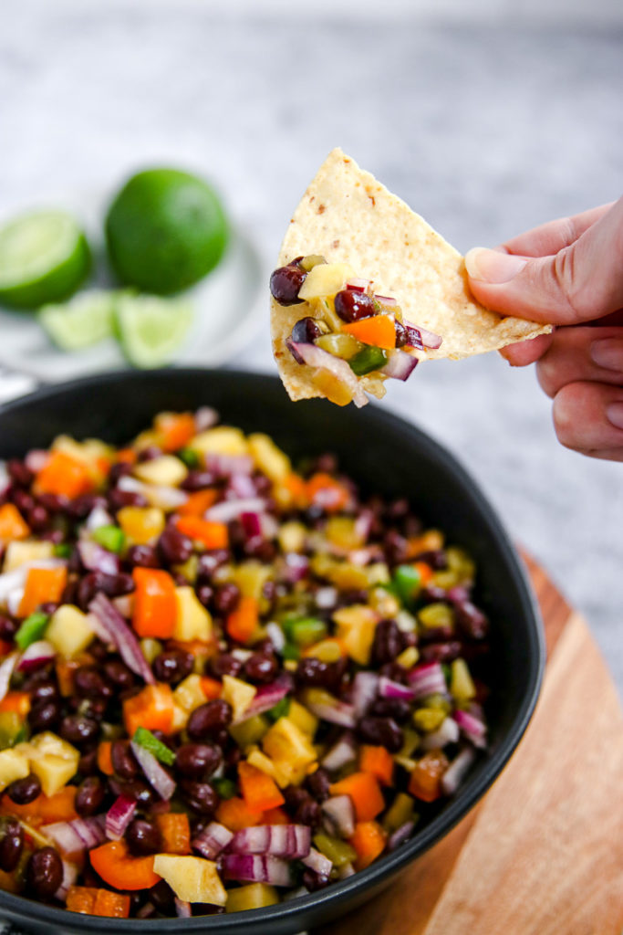 a hand holding a tortilla chip with mango black bean salsa on it