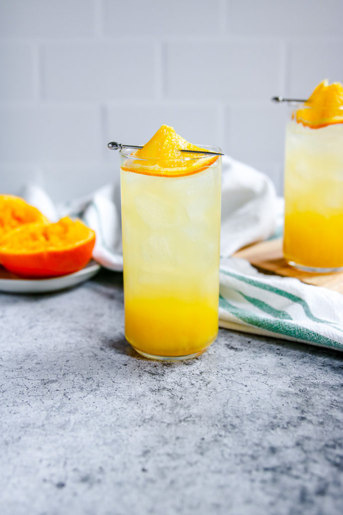 a highball glass filled with an orange crush and an orange slice on top