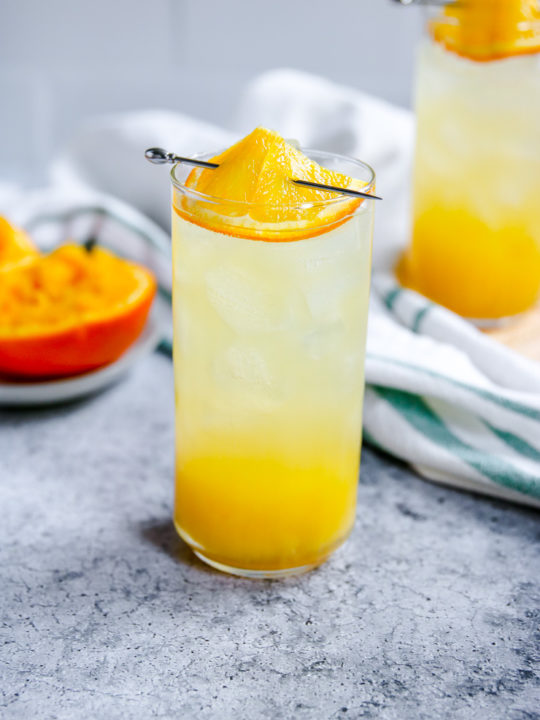 an orange crush in a highball glass with squeezed oranges behind it