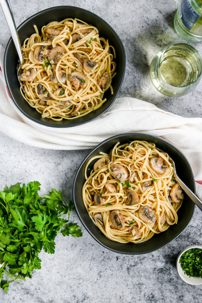 two bowls of white wine mushroom pasta next to a glass of white wine and parsley
