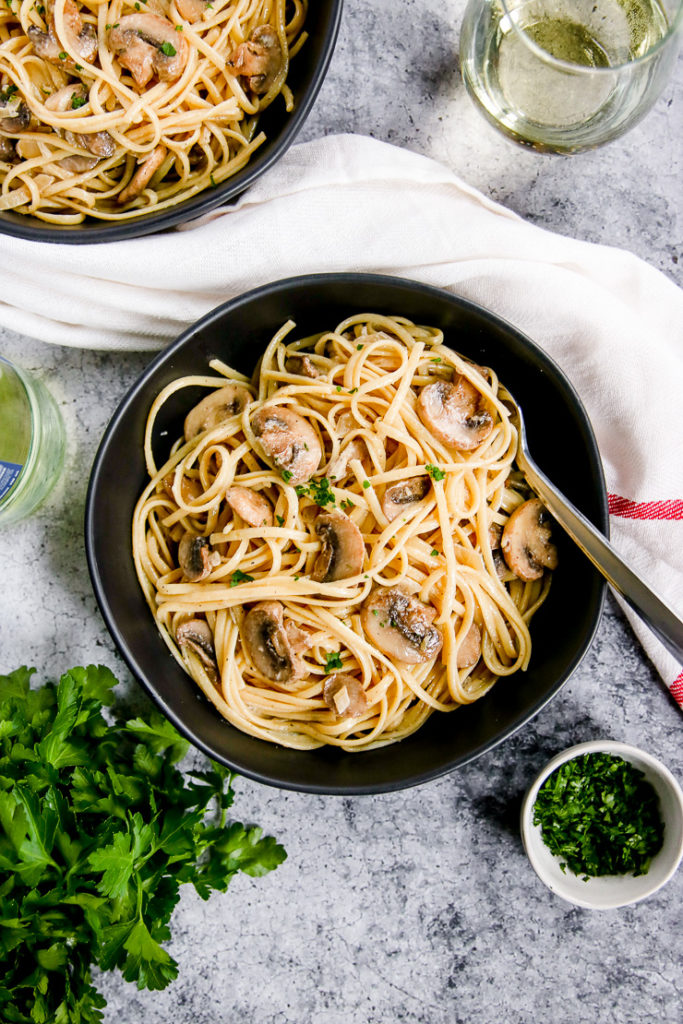 white wine mushroom pasta in a black bowl next to a glass of white wine and parsley