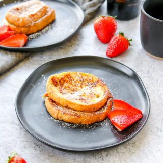 two plates of baileys french toast with strawberries, a mug of coffee, and bottle of baileys