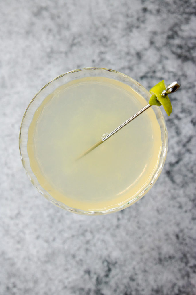 overhead shot of the coupe glass full of pastel elderflower gimlet and a cocktail pick