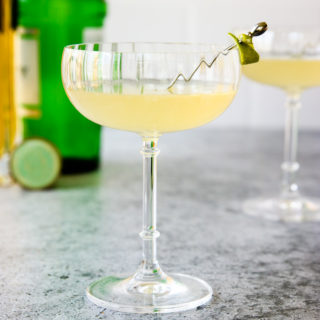 a glass of elderflower gimlet with a lime rind on a cocktail pick and green gin bottle behind it