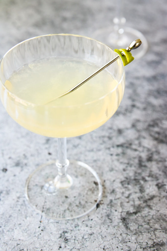 pastel yellow elderflower gimlet in a coupe glass