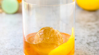a rocks glass with a lemon peel, round ice cube, and elderflower old fashioned
