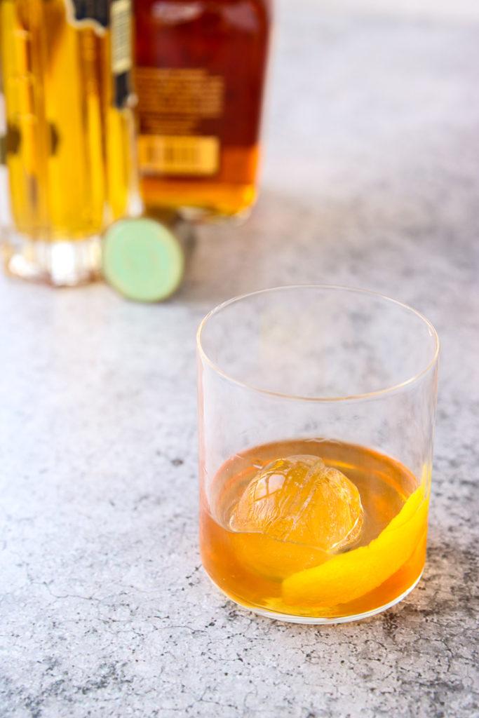 an elderflower old fashioned in a rocks glass in front of a bourbon and elderflower liquor bottle