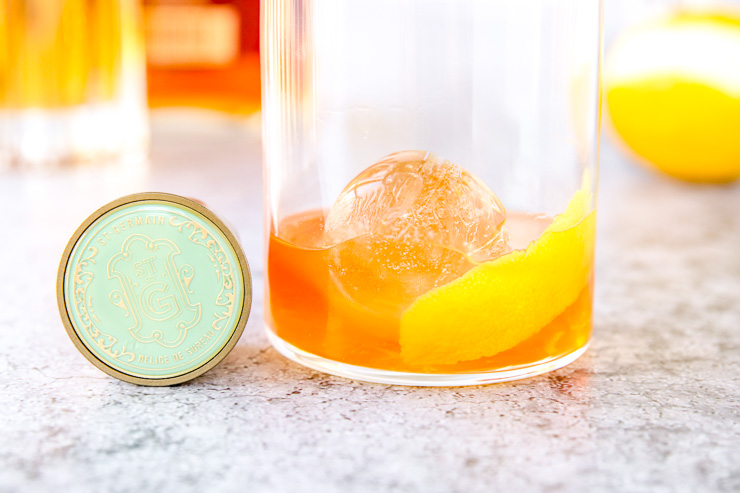 a close up of an elderflower old fashioned and the teal lid of st. germain
