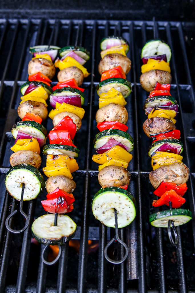four veggie skewers sitting on a grill over a small flame