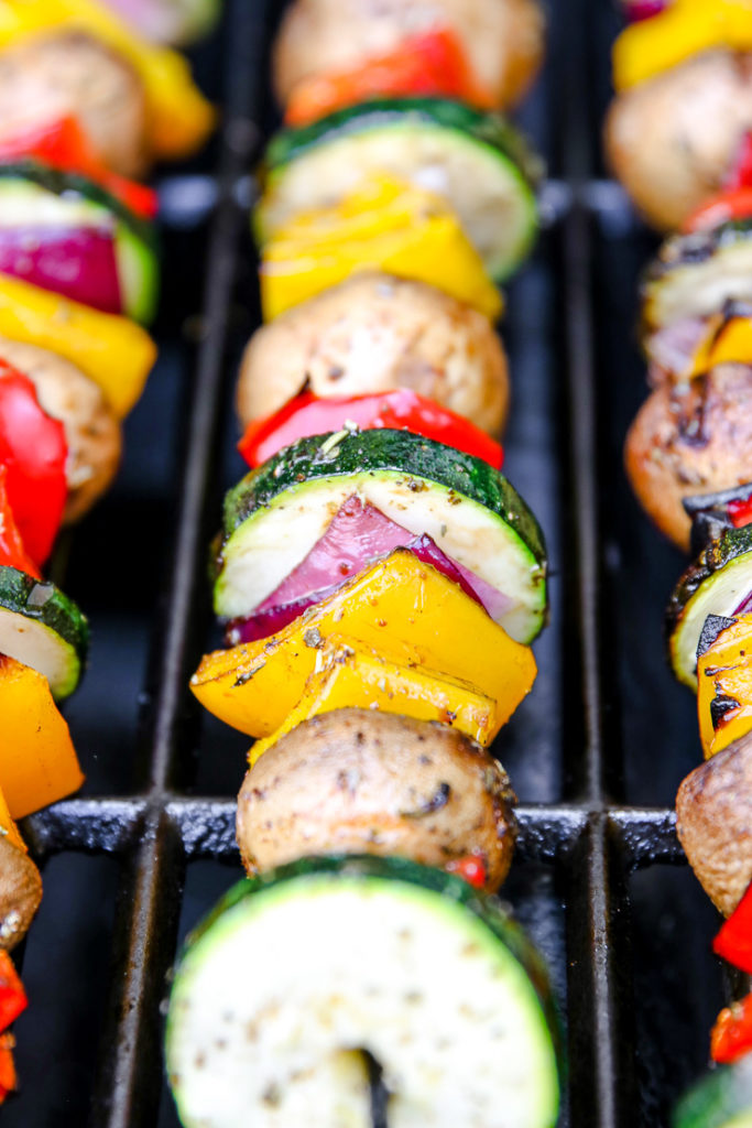 a close up of a skewer with veggies on the grill