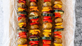 four grilled veggie skewers on wax paper on a wooden platter