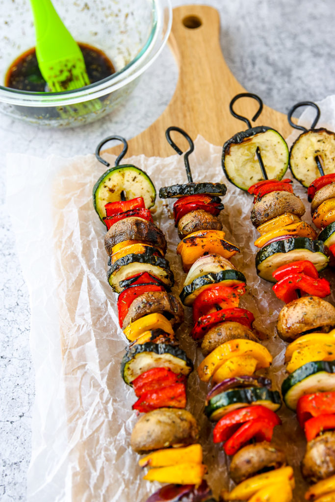 a bowl of marinade with a silicone brush next to four skewers of grilled veggies