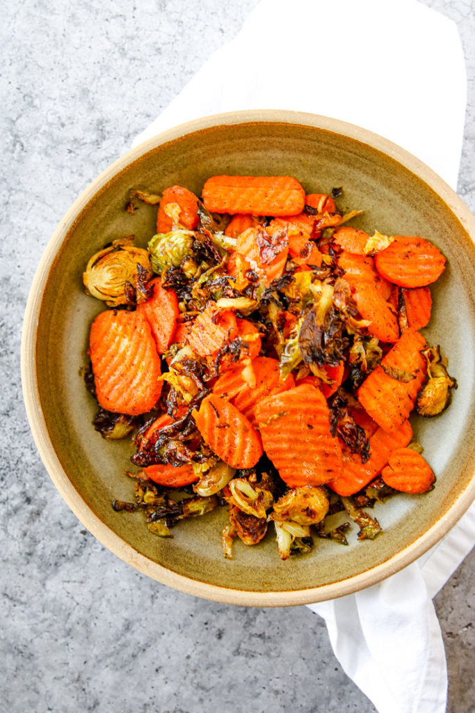 an earthy green bowl on a white napkin with a scoop of roasted brussels sprouts and carrots