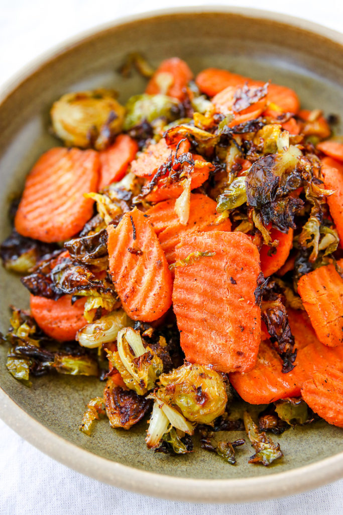a close up of roasted shaved brussels sprouts and ridged carrot chips