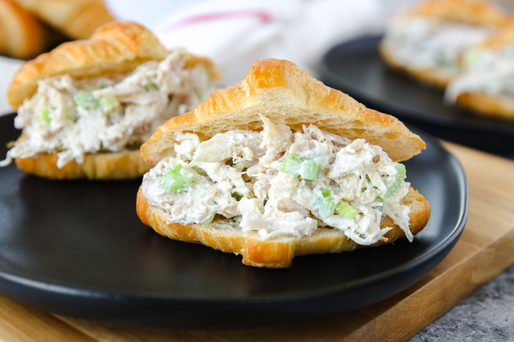 a close up of rotisserie chicken salad in a croissant