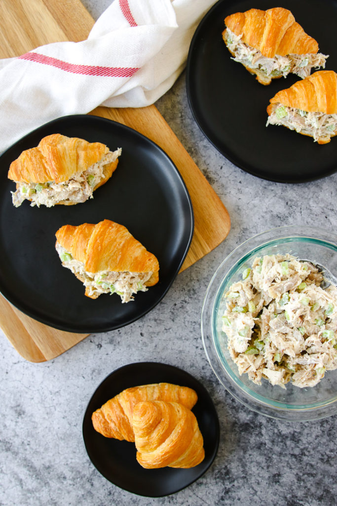 an overhead of three black plates with croissants and rotisserie chicken salad