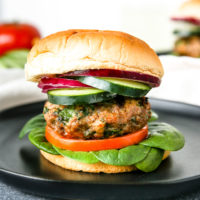 layers of spinach, tomato, a spinach feta turkey burger, cucumber, and red onion on the bun