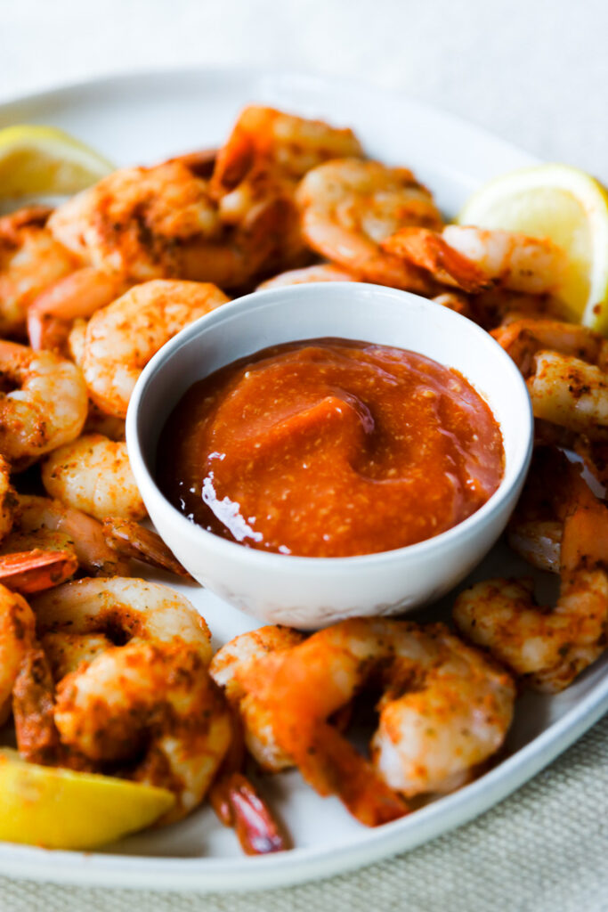 a small bowl of cocktail sauce on a plate of steamed shrimp and lemons
